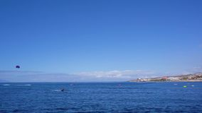 Clean sea water. Tenerife coast and clean sea water and clear blue sky with someones paragliding stock video