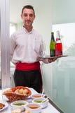 Tenerife, España, enero de 2015: camarero que lleva una bandeja de vino encendido foto de archivo