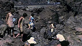 Tenerife island tourists on Teide volcano. Tenerife, Spain - Circa 1976: tourists on the lava stone of Teide Volcano in Teide National Park. Touristic bus with stock footage