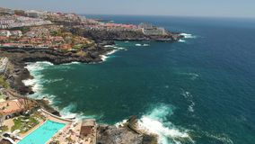 Tenerife, Los Gigantes, Spain - May 18, 2018: Aerial view rocky coast and hotels, Canary islands. 4K drone shot from above stock video footage