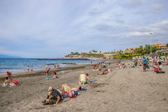 TENERIFE, SPAIN - DEC 2012: People sunbathing on the beach in resort Playa de Las Americas on December 6 Stock Image