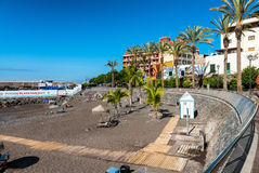 TENERIFE, SPAIN - SEPTEMBER 7, 2016: Tourists enjoy volcanic beach of Playa San Juan. Tenerife attracts 5 million people annually stock photography