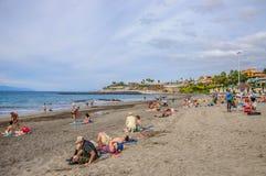 TENERIFFA, SPANIEN - DEZEMBER 2012: Leute, die auf dem Strand in Erholungsort Playa De Las Amerika am 6. Dezember ein Sonnenbad n Stockbild