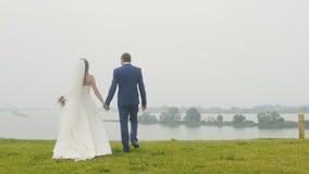 Tenersi per mano andante della sposa e dello sposo al fiume sull'alta collina stock footage