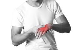 Tenersi per mano dell'uomo Il dolore nel polso il focolare è highlighte fotografia stock libera da diritti