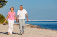 Tenersi per mano di camminata delle coppie senior felici su una spiaggia immagini stock libere da diritti