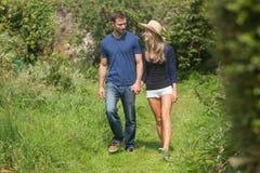 Tenersi per mano di camminata delle coppie sveglie Fotografia Stock
