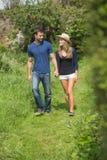 Tenersi per mano di camminata delle coppie sveglie Fotografia Stock Libera da Diritti
