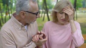 Tenersi per mano preoccupantesi del marito della moglie malata anziana, morbo di Aalzheimer, supporto della famiglia stock footage