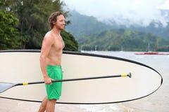 Tenez l'homme de plage de panneau de palette faisant le paddleboard image libre de droits