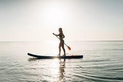 Tenez la femme de panneau de palette paddleboarding sur Hawaï se tenant heureuse sur le paddleboard sur l'eau bleue Photos stock