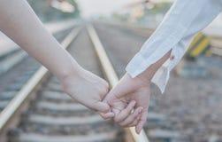 Tenez la main le long du chemin de fer Images libres de droits