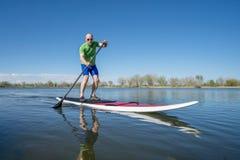 Tenez la séance d'entraînement de paddleboard Image libre de droits