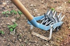 Tenez le premier rôle le cultivateur de main pour travailler le sol, sarclez le jardin photos stock