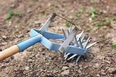 Tenez le premier rôle le cultivateur de main pour travailler le sol, sarclez le jardin image stock