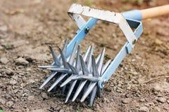 Tenez le premier rôle le cultivateur de main pour travailler le sol, sarclez le jardin photo libre de droits