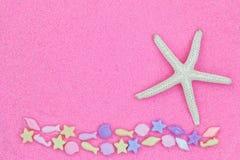 Tenez le premier rôle les poissons, connus sous le nom d'étoiles de mer, et les perles d'espèce marine sur l'aileron rose Photographie stock