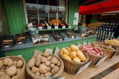 Tenez-vous avec des paniers d'agriculteurs complètement de pomme de terre et d'autres légumes au marché de ville Photo libre de droits