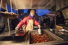 Tenez-vous avec la châtaigne chaude - spécialité d'hiver pendant le Noël à Prague images stock