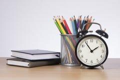 Tenez-vous avec les crayons colorés entre les livres et l'horloge Image libre de droits