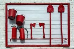 Tenez-vous sur le mur du bâtiment, avec l'équipement nécessaire au cas où vous devriez vou'éteindre le feu image libre de droits