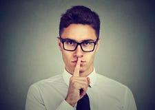 Tenga il mio segreto Dito della tenuta dell'uomo d'affari sulle labbra che esaminano macchina fotografica immagini stock