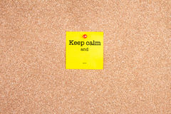 Tenga la calma e su una nota appiccicosa gialla sul bordo del sughero Fotografia Stock