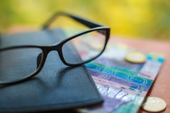 Tenge, Kazakh money and glasses on the table Royalty Free Stock Images