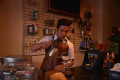 TENGGARONG, INDONESIË - MEI 2017: De knappe koffie die van de baristakoffie kop en het maken van het Concept van de koffiedienst  royalty-vrije stock foto