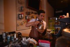 TENGGARONG, INDONESIË - MEI 2017: De knappe koffie die van de baristakoffie kop en het maken van het Concept van de koffiedienst  royalty-vrije stock afbeelding
