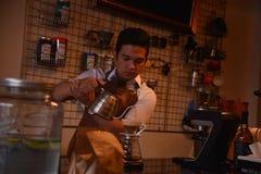 TENGGARONG, INDONESIA - MEI 2017: Caffè bello del caffè di barista che prepara tazza e che fa del concetto di servizio di caffè p Immagine Stock