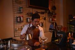 TENGGARONG INDONESIEN - MEI 2017: Stiligt baristakafékaffe som förbereder koppen och in gör av begreppet för kaffeservice för kun Arkivfoto