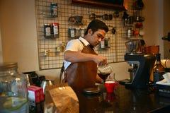 TENGGARONG, INDONEZJA - MEI 2017: Przystojna barista kawiarni kawa Fotografia Royalty Free