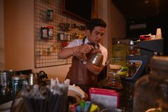 TENGGARONG, INDONEZJA - MEI 2017: Przystojnego barista cukierniana kawowa przygotowywa filiżanka i robić kawowej usługa pojęcie d Zdjęcia Royalty Free