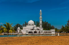 Tengku Zahrah Tengah Mosque before sunset. Beautiful white mosque with reflection in the lake during clean blue sky Royalty Free Stock Images