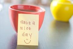 Tenha um dia agradável com coffe do sorriso e do copo Fotografia de Stock