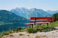 Tenha um resto nos cumes suíços com uma vista bonita em um banco vermelho de madeira fotografia de stock royalty free