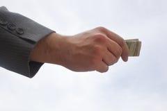 Tenir l'argent Photographie stock libre de droits