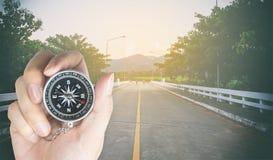 Tenir la boussole sur une route de campagne pour la direction Photos libres de droits