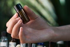 Tenir la bouteille d'huile essentielle images libres de droits