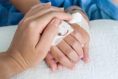 Tenir la main patiente de garçon avec l'intravenous salin (iv) dans le hospita Photographie stock libre de droits