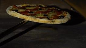 Tenir la pizza sur la pelle à fer à l'intérieur du four traditionnel dans le mouvement lent clips vidéos