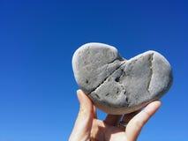 Tenir la roche de coeur sur le ciel bleu Images libres de droits