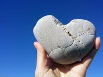 Tenir la roche de coeur sur le ciel bleu Photo stock