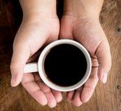 Tenir la tasse de café chaude Image stock