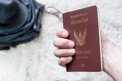 Tenir le passeport thaïlandais Photographie stock libre de droits