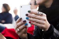 Tenir le smartphone avec les vernis à ongles colorés multi image libre de droits