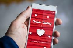 tenir le smartphone en ligne de datation Images stock