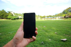 Tenir le téléphone intelligent mobile dans la main masculine Photos stock