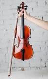 Tenir le violon avec l'arc sous le piano à queue blanc avec le fond de mur de briques Photos stock
